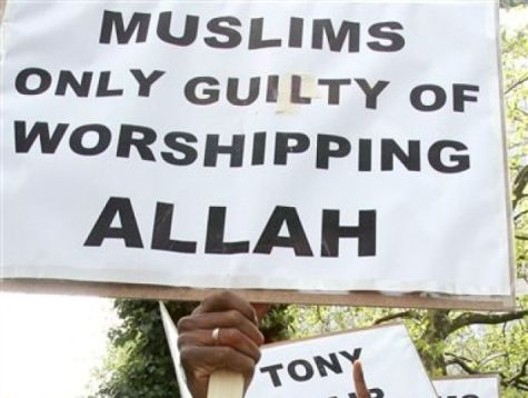 Foto van een demonstratiebord met hierop de tekst 'muslims only guilty of worshipping allah'.